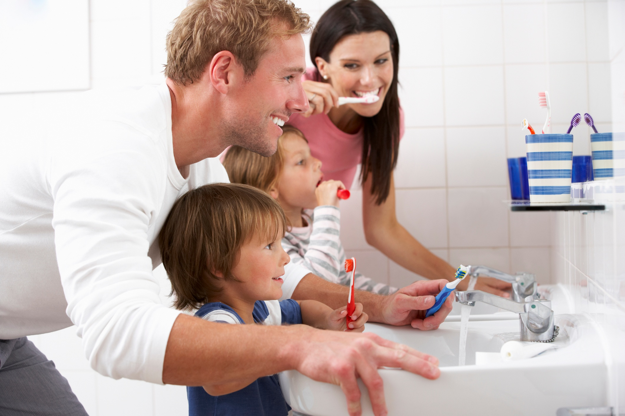 A mother and father teaching their children how to brush their teeth in bathroom