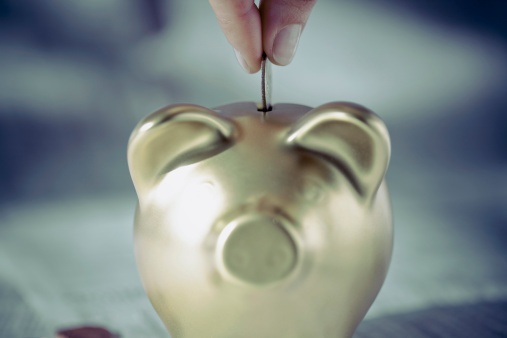 126530543_Persons_hand_putting_coin_into_a_piggy_bank.jpg